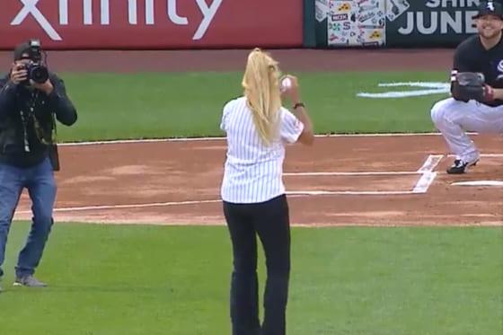 女性が投じたボールは写真左側のカメラマンへ…(画像はスクリーンショット)