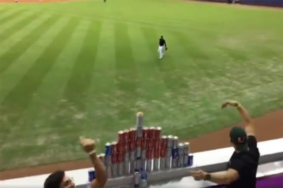 外野フェンスに作ったビール缶ピラミッドにボールを投げるよう催促するファン(画像はスクリーンショットです)