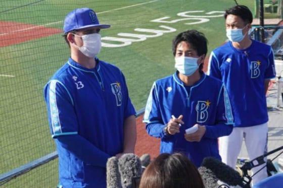 練習試合後、マスク姿で報道陣の取材に応じるDeNAのタイラー・オースティン(左)【写真:宮脇広久】