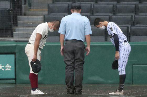 両校の主将に降雨コールドを説明した山口智久さん(中央)【写真:共同通信社】